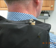 Photo 2 - male officer wears used vest showing bullet fragment inpacted on the back of the neck line